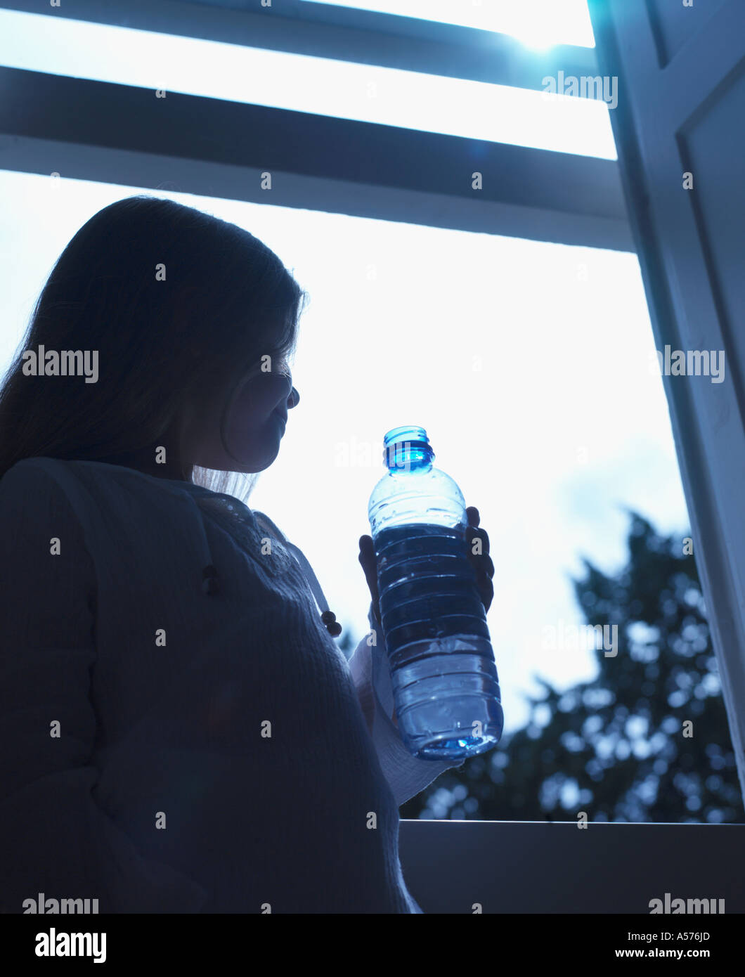 Girl holding a bottle of water looking outside a window Stock Photo