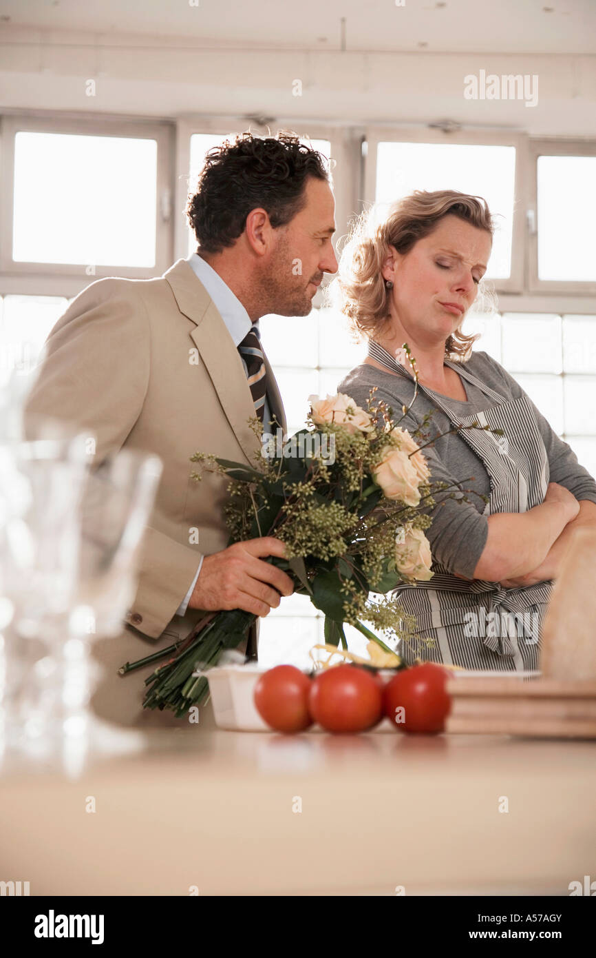 Mature couple in kitchen with flower bouquet - Stock Image