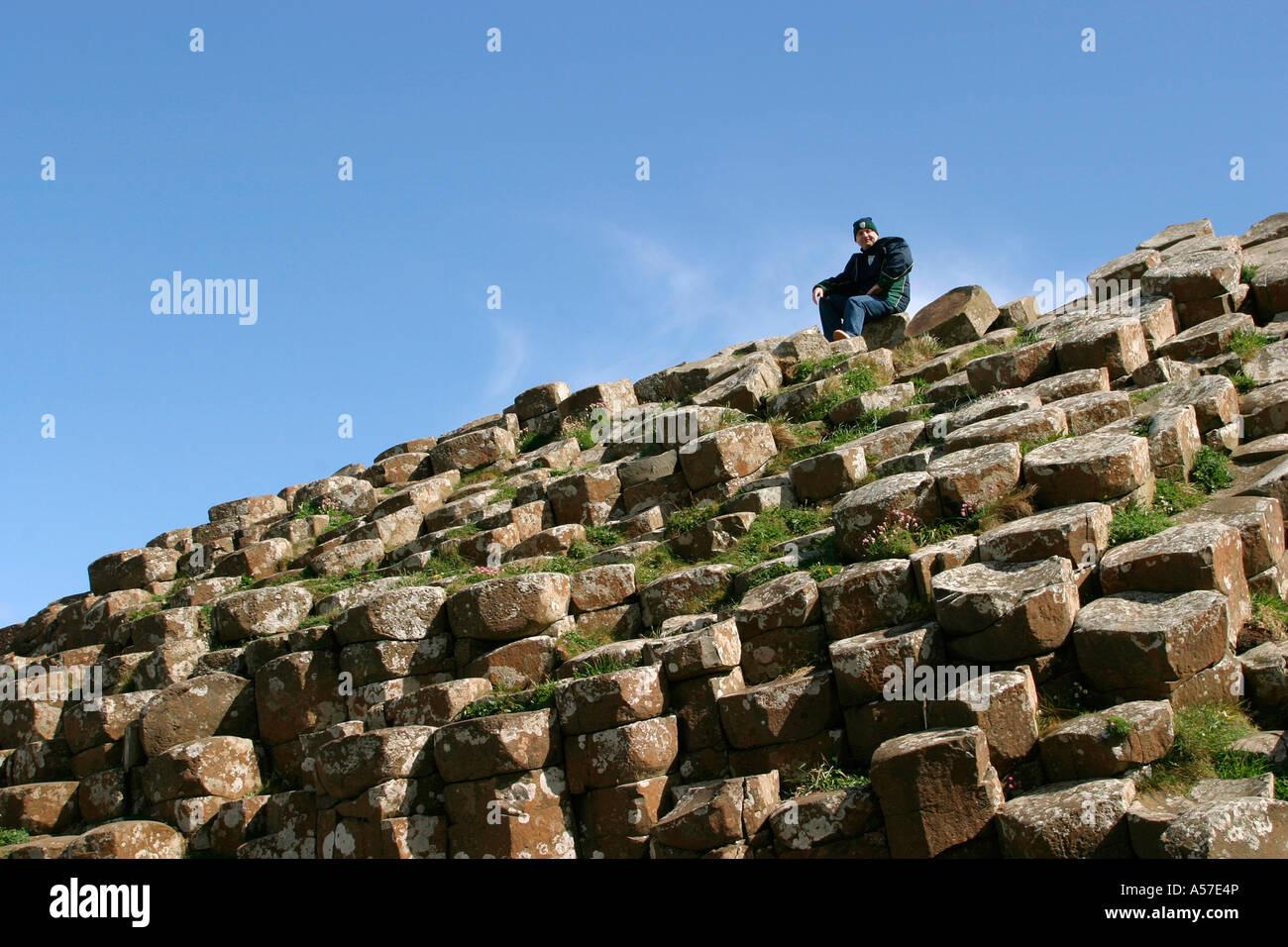 County Antrim Giants Causeway man sat on rocks Stock Photo