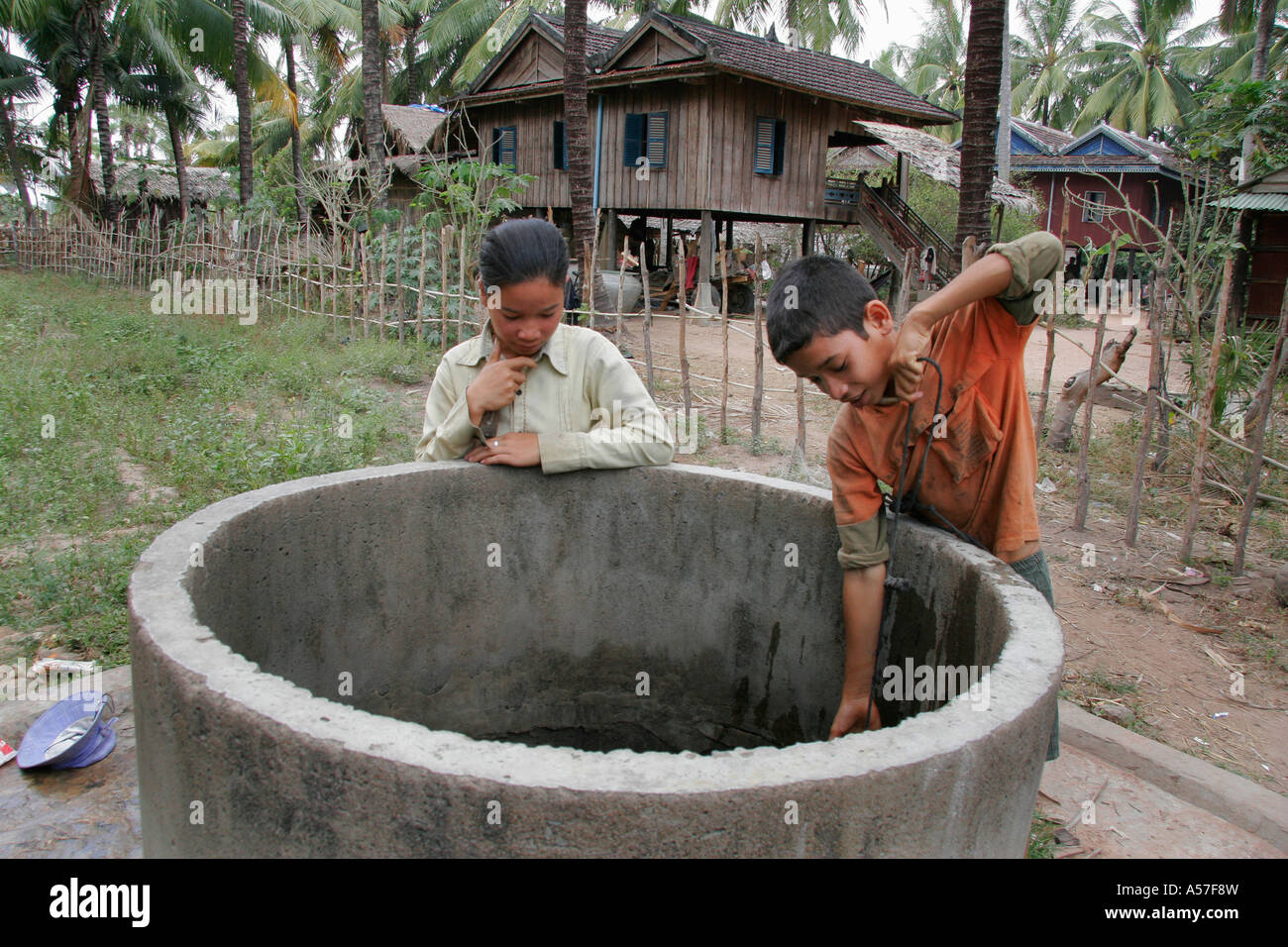 Painet je2207 cambodia day life boy 14 year old kun nob collecting water well kampot province 2006 labor labour Stock Photo
