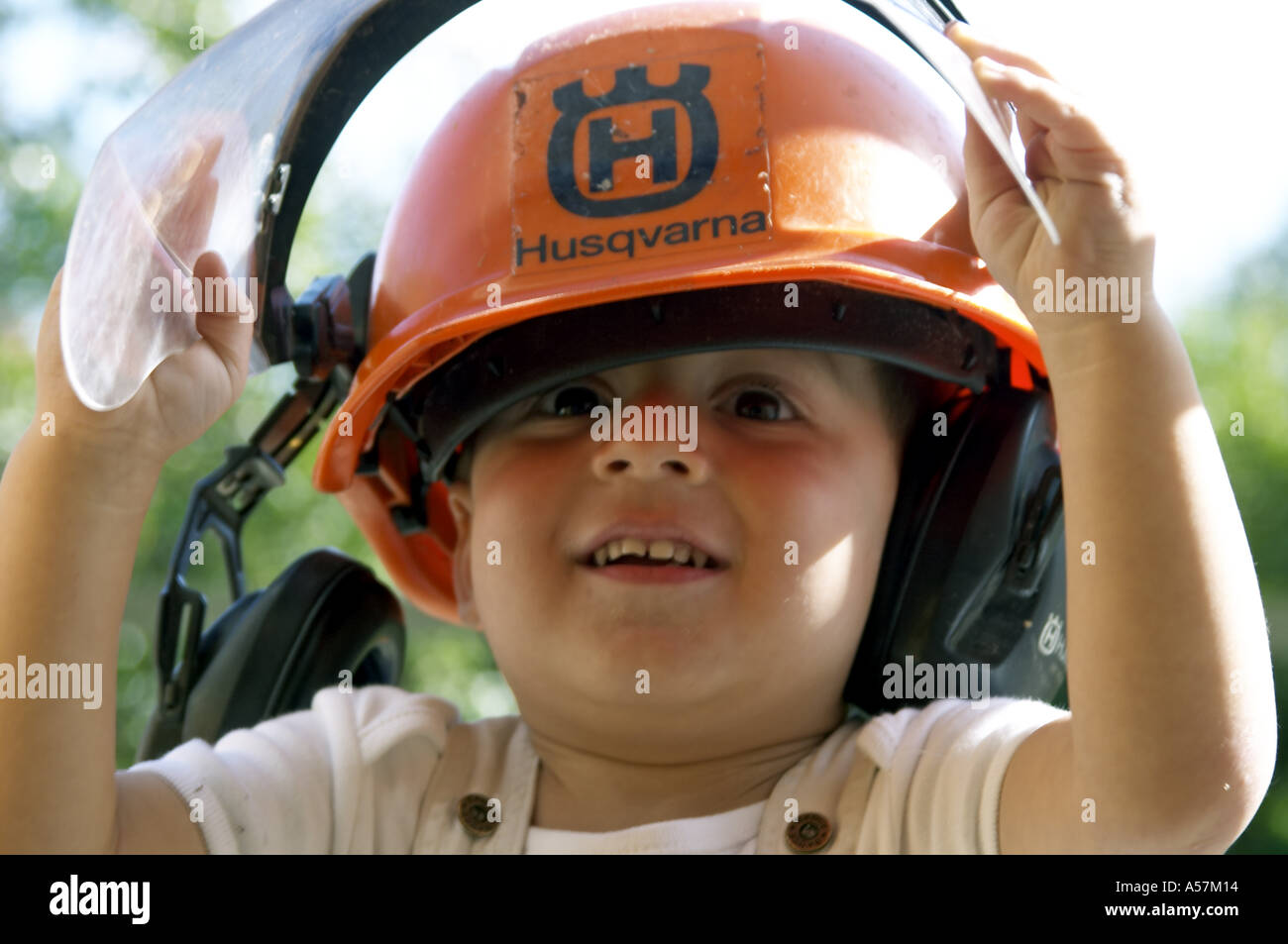 Young boy wearing orange protective Husqvarna construction hard hat and ear protectors Humourous amusing playing laughing an - Stock Image
