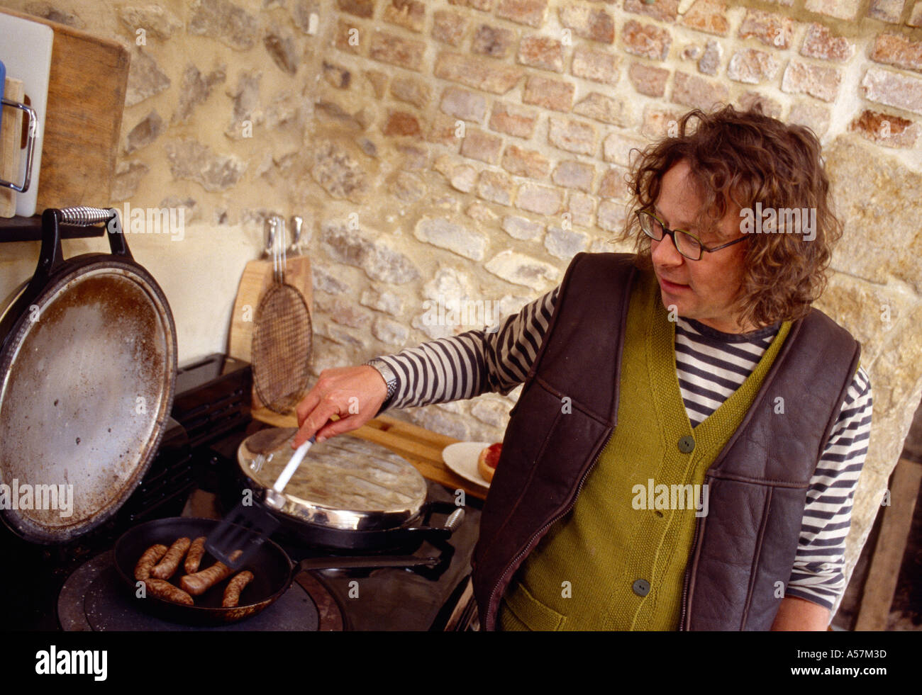 Hugh Fearnley Whittingstall Cooking sausages on Aga in farm kitchen Keywords location personality people Somerset - Stock Image