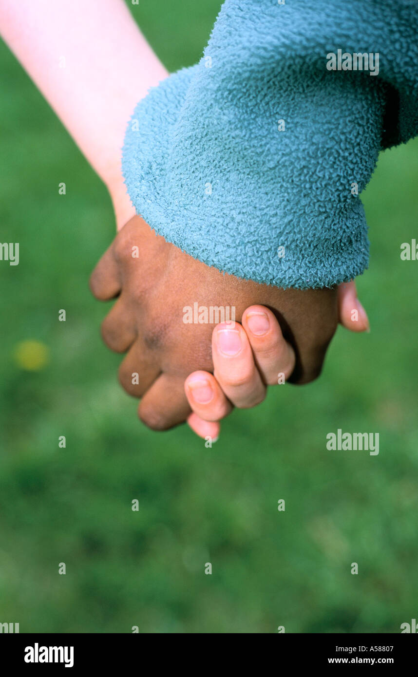 Close up of black and white friends holding hands - Stock Image