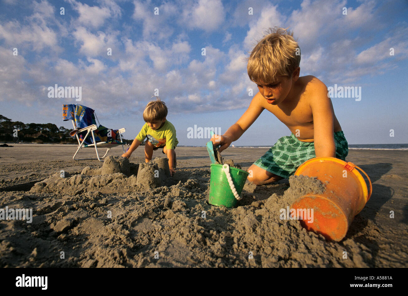 Two young boys playing in the sand and making sandcastles at the beach - Stock Image