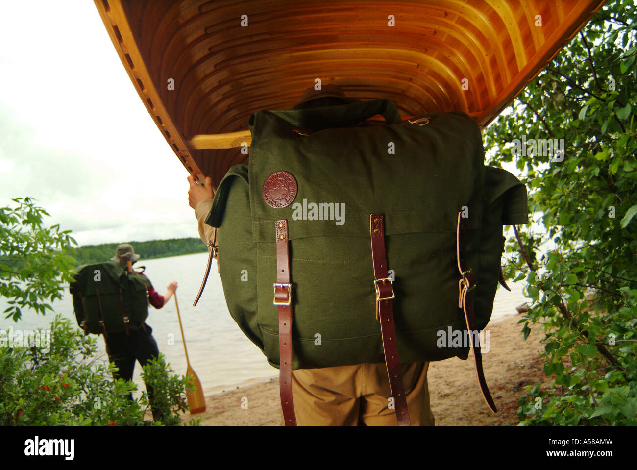 Portaging a wooden canoe in Boundary Waters Canoe Area Wilderness BWCAW Minnesota - Stock Image