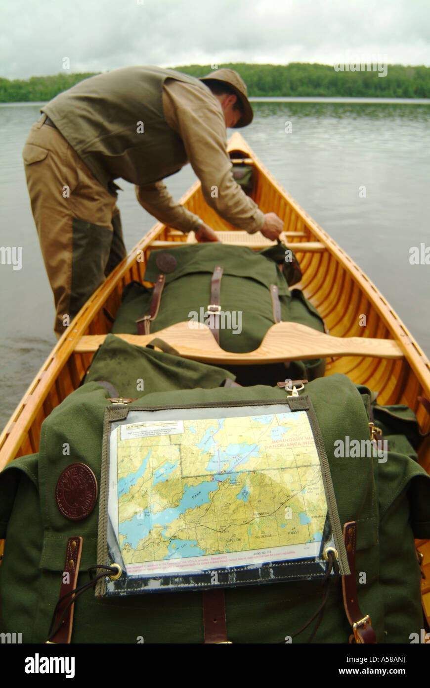 Canoer Loading his pack in Boundary Waters Canoe Area Wilderness BWCAW Minnesota - Stock Image