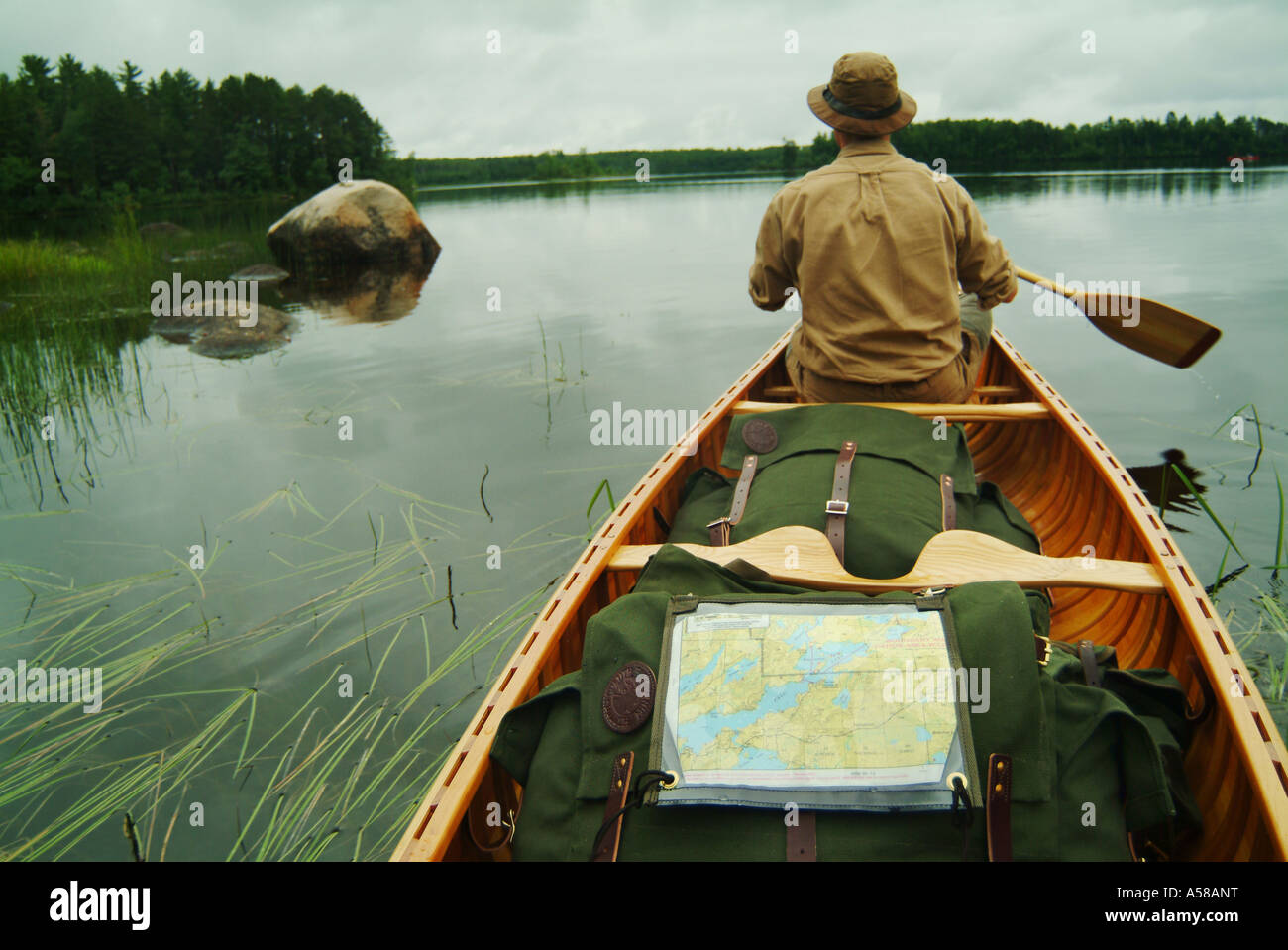 Paddling a canoe in Boundary Waters Canoe Area Wilderness BWCAW Minnesota - Stock Image