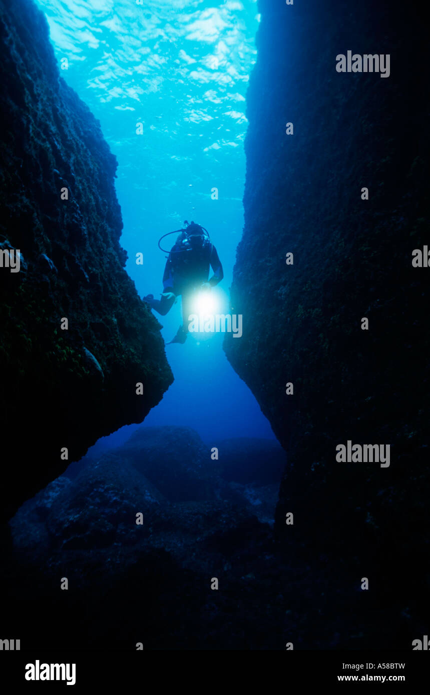 Underwater scuba diver shines a light while swimming through a cave. - Stock Image