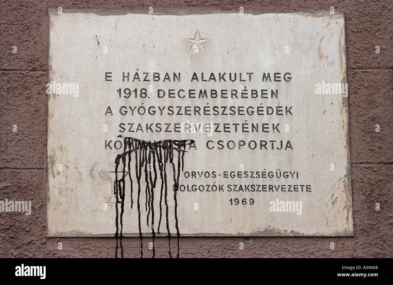The word communist defaced in a sign in post- Communist Budapest, Hungary - Stock Image
