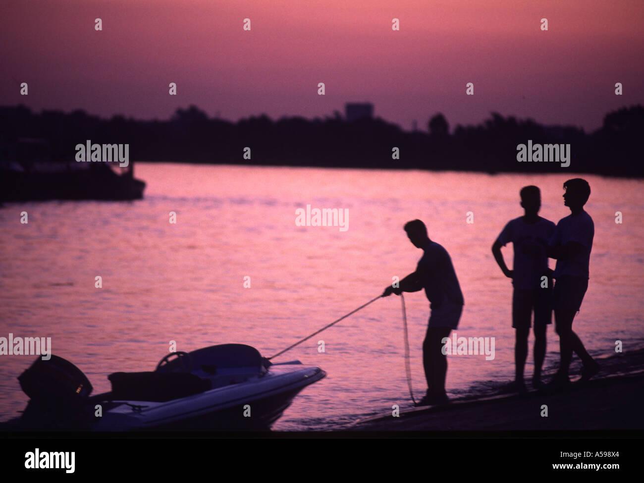 men tying up boats on pontoon river thames at putney london uk - Stock Image
