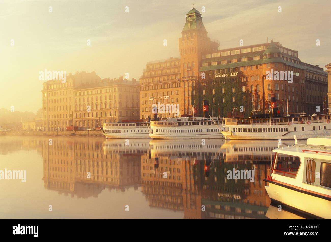 Ferryboats anchored at Nybroviken with SAS Radisson Hotel at sunrise in Stockholm - Stock Image