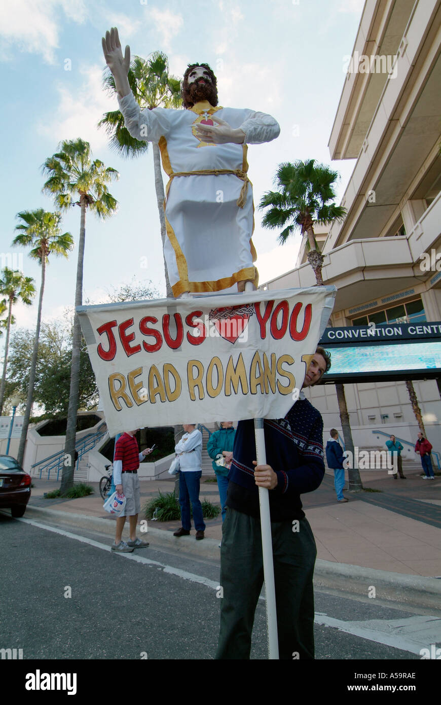 Jusus loves you message on sign of male demonstrator in front of the Tampa Florida Convention Center - Stock Image