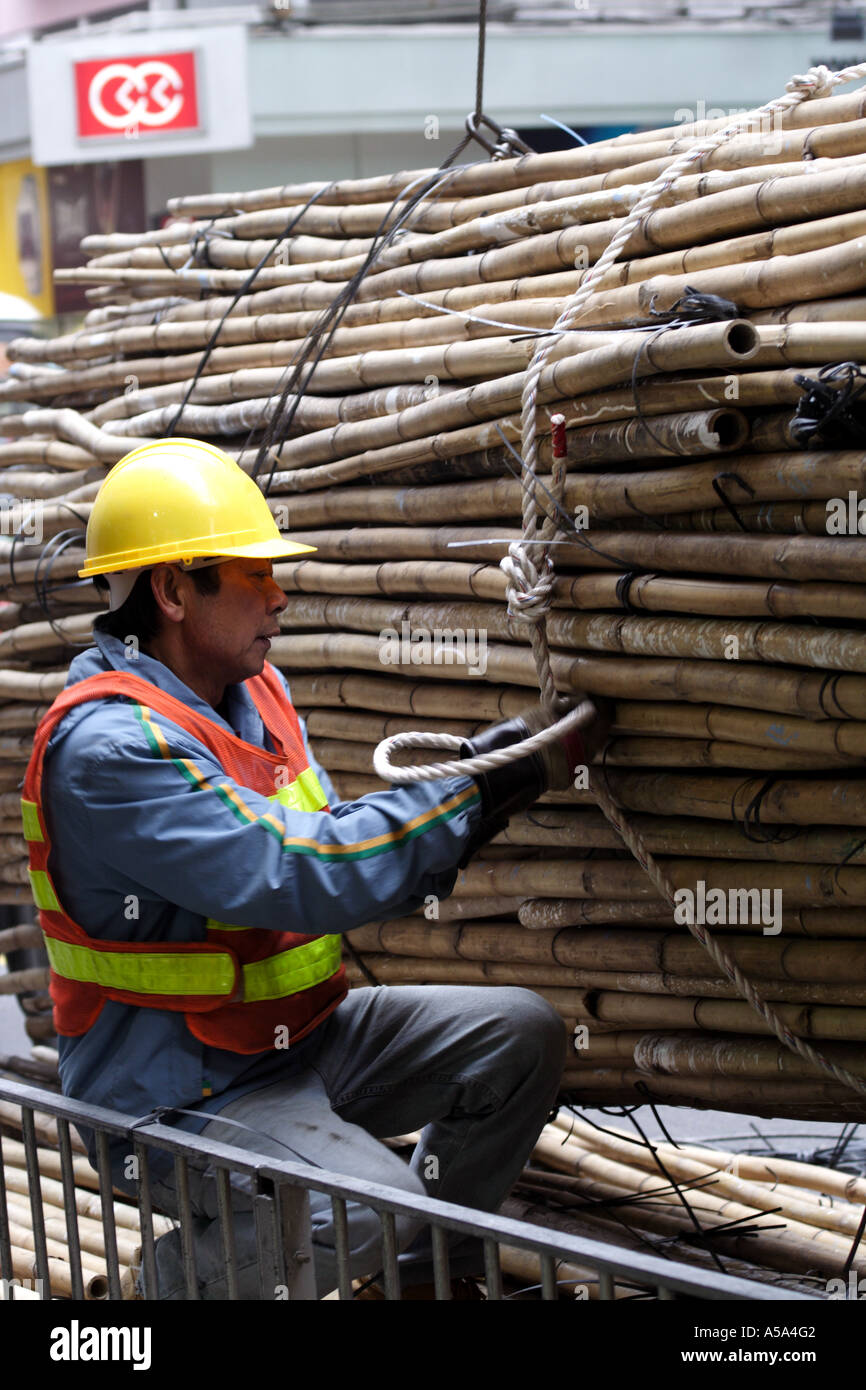 Workman guides mechanical arm in the lifting of bamboo used for scaffolding, Hong Kong, SAR - Stock Image