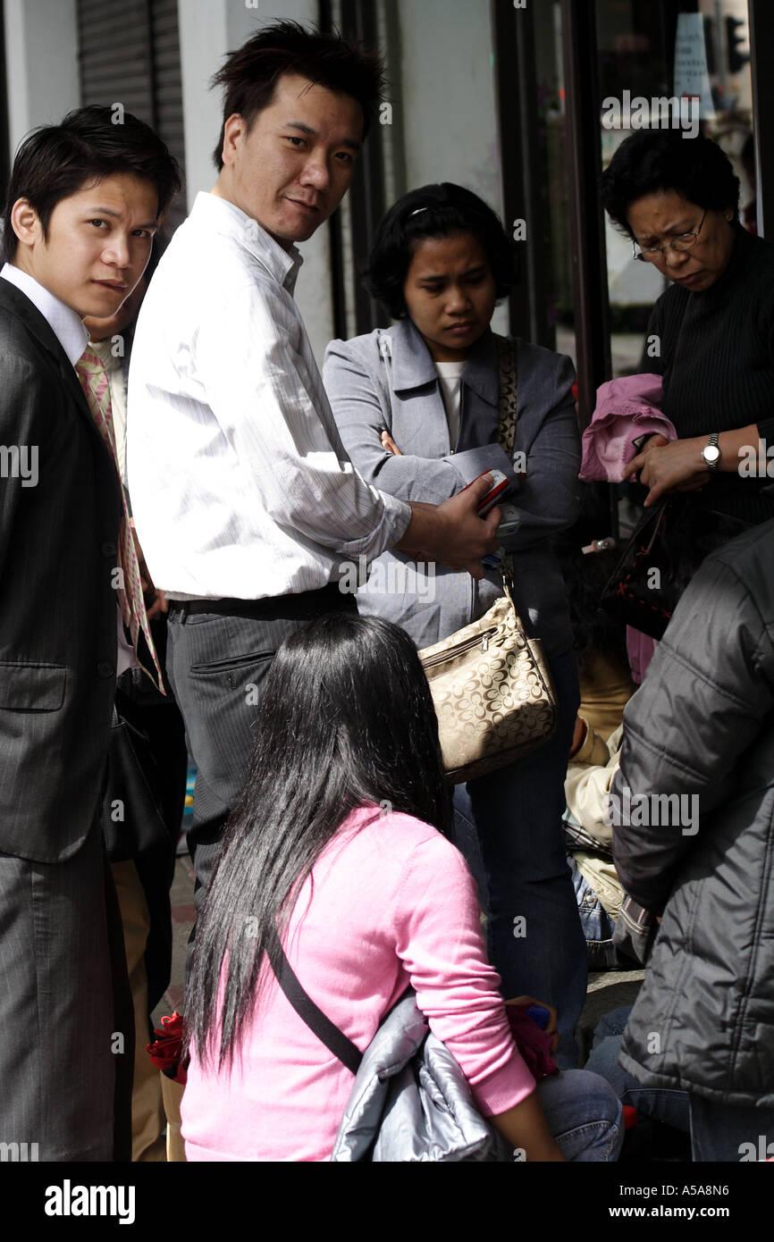Hong Kong Chinese marketing mobile phones to Filipina Amahs enjoying their day off, Hong Kong SAR - Stock Image