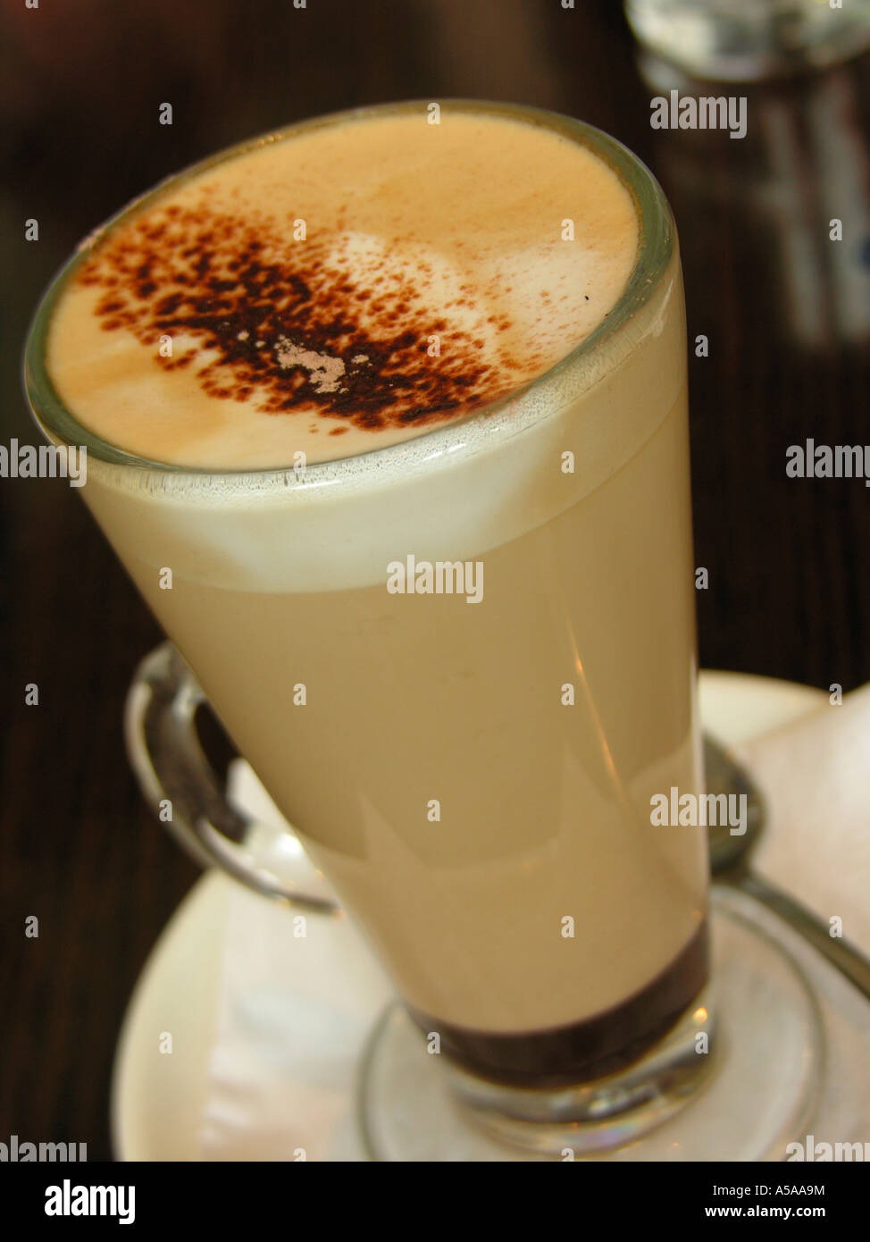 Cafee latte with frothed milk in high glass cup on white saucer - Stock Image