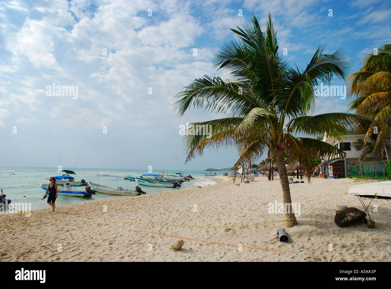Beach life at the 10 mile long beach in Playa del Carmen Mexico Boats palm tree - Stock Image
