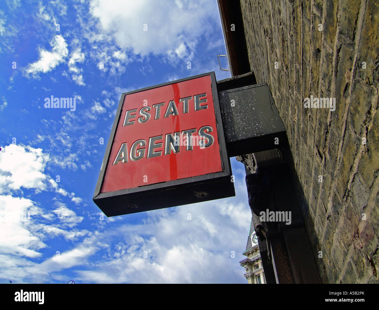 Bright Red Estate Agents sign against blue sky. with copy space on all sides - Stock Image