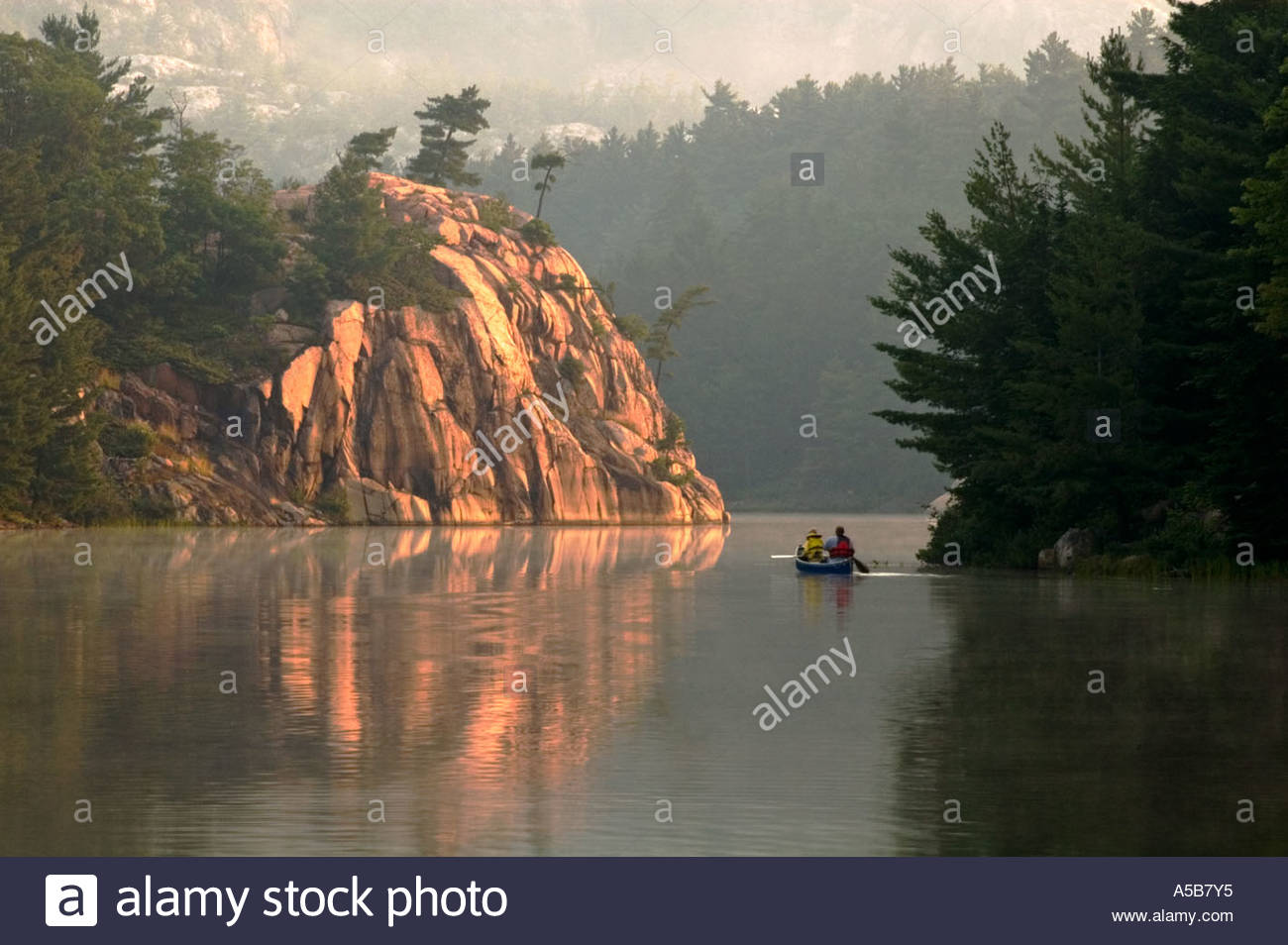 George Lake at dawn with canoeists. Killarney Provincial Park Ontario Stock Photo