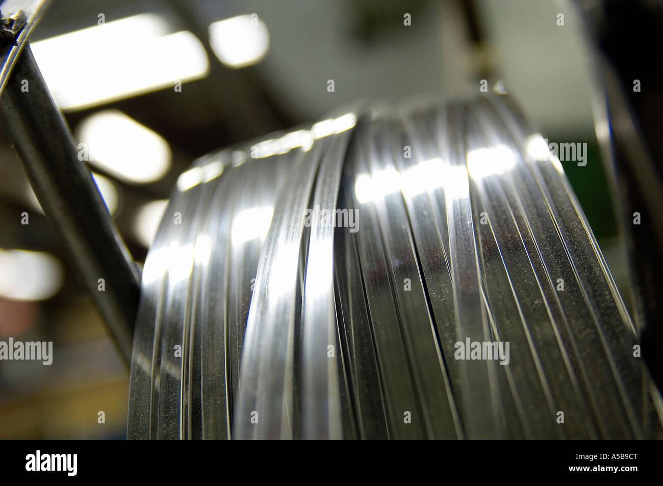 Long thin metal on spool. - Stock Image