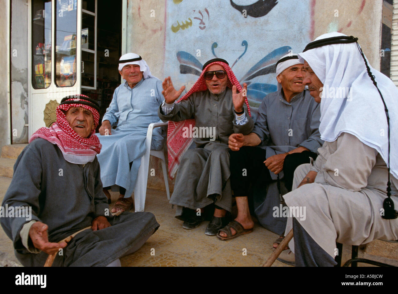 Men gathering, partially obscured mural of Hafez Al Assad in background, Syria Stock Photo
