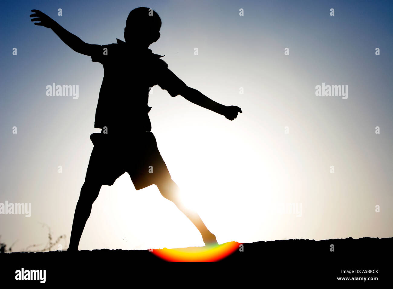 Silhouette profile of a young Indian boy dancing against hazy sun setting background showing lens flare. India - Stock Image