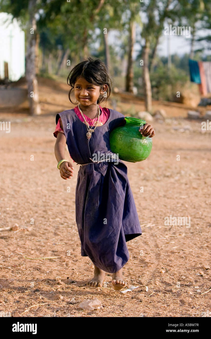Young poor Indian girl carrying water pot from a village water tap. Andhra Pradesh, India - Stock Image