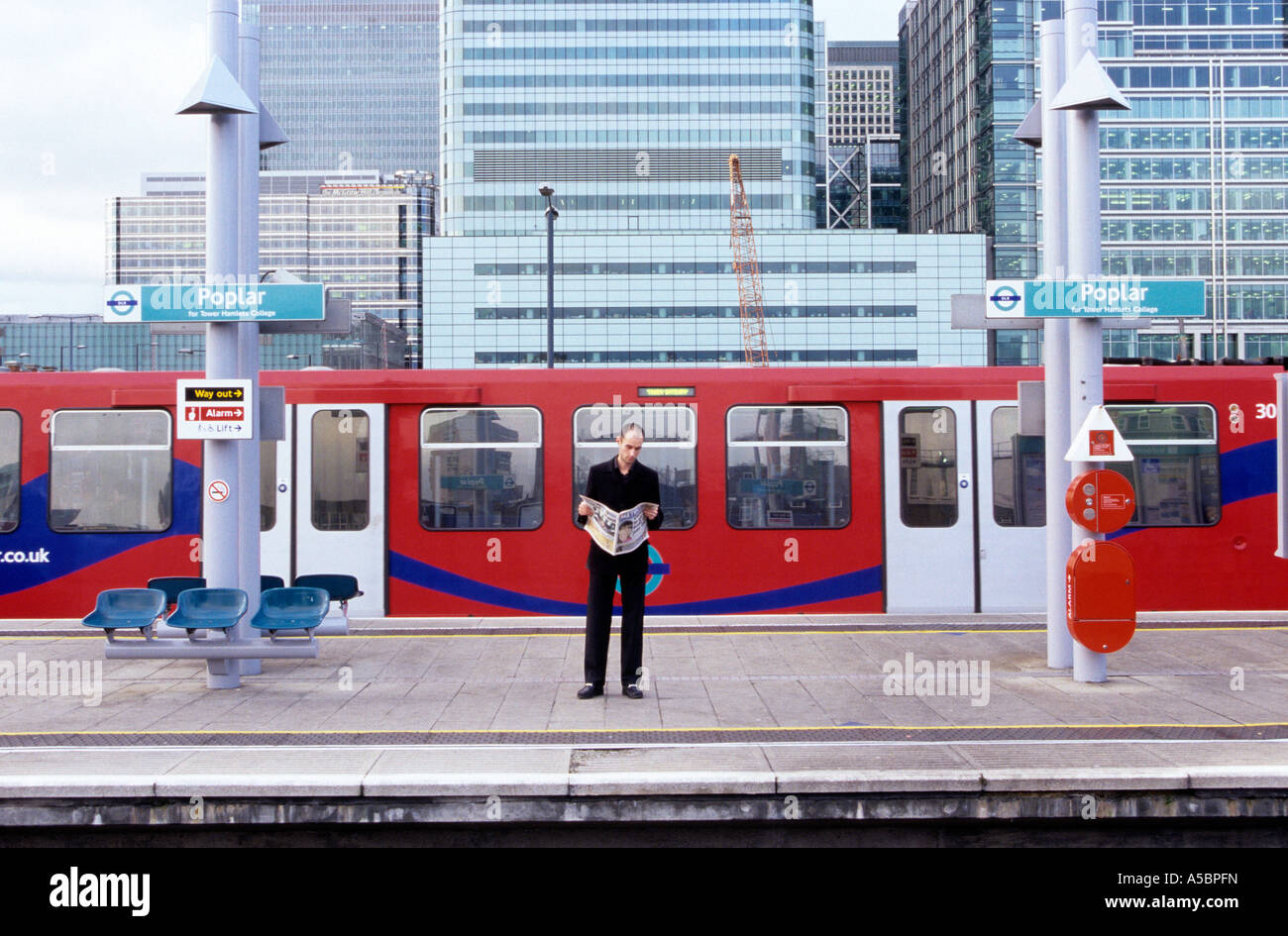 A man reading a newspaper while waiting for the train at the Poplar station in London - Stock Image