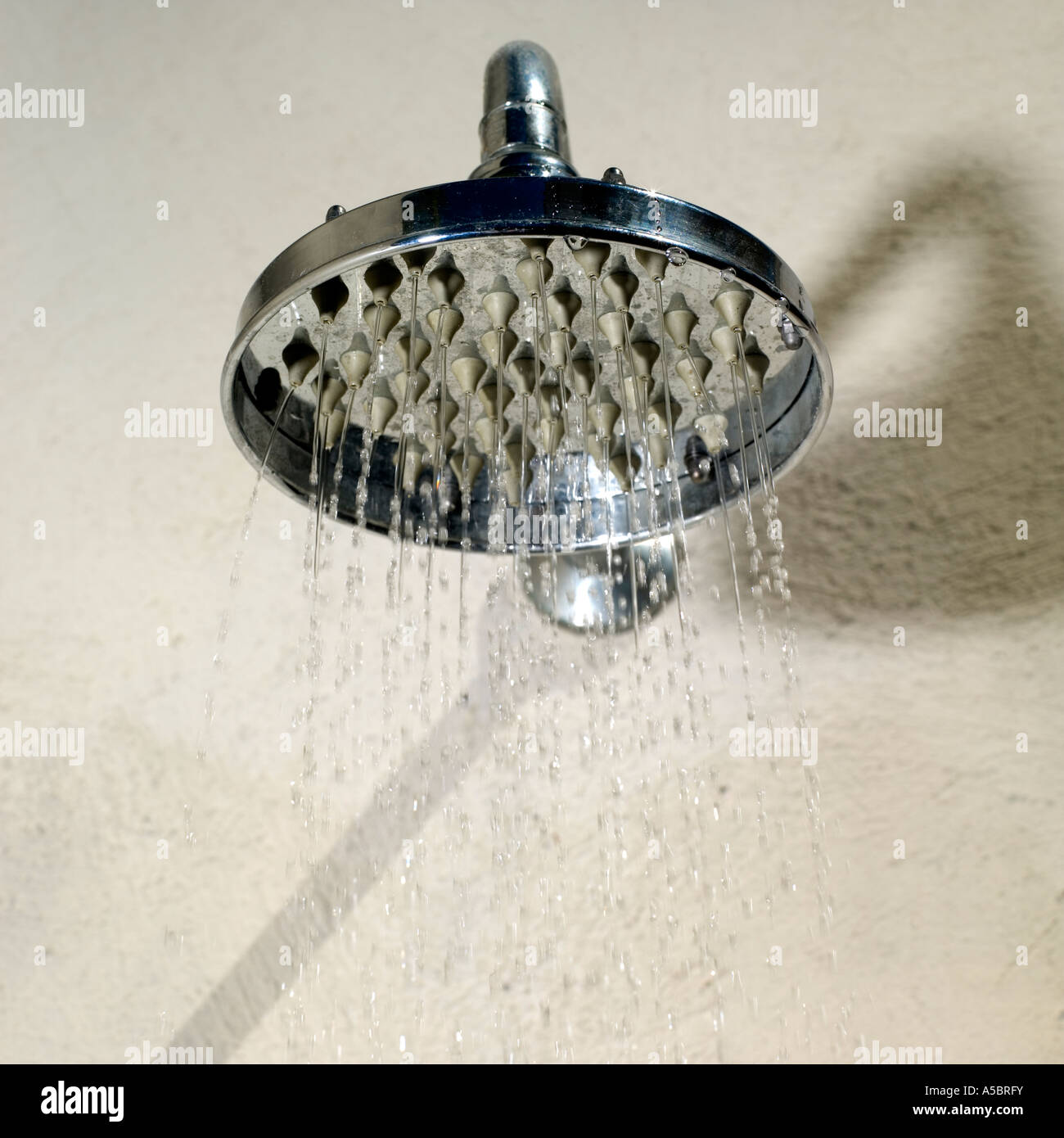 Water jet from wide shower head conservation shortages and rationing, political global issue - Stock Image