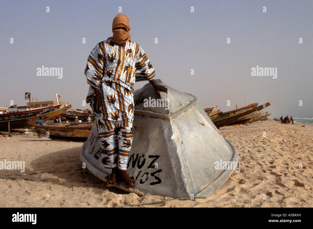 Mauritanian fisherman in traditional clothing leaning against upturned fishing boat on beach, portrait, Nouakchott, - Stock Image