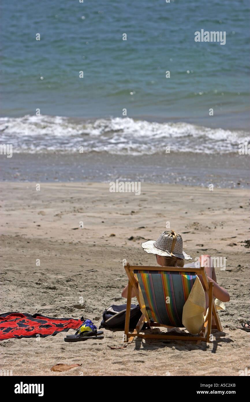 Woman in local handicraft sun hat reads book in deck chair on beach Ko Jum island Thailand - Stock Image