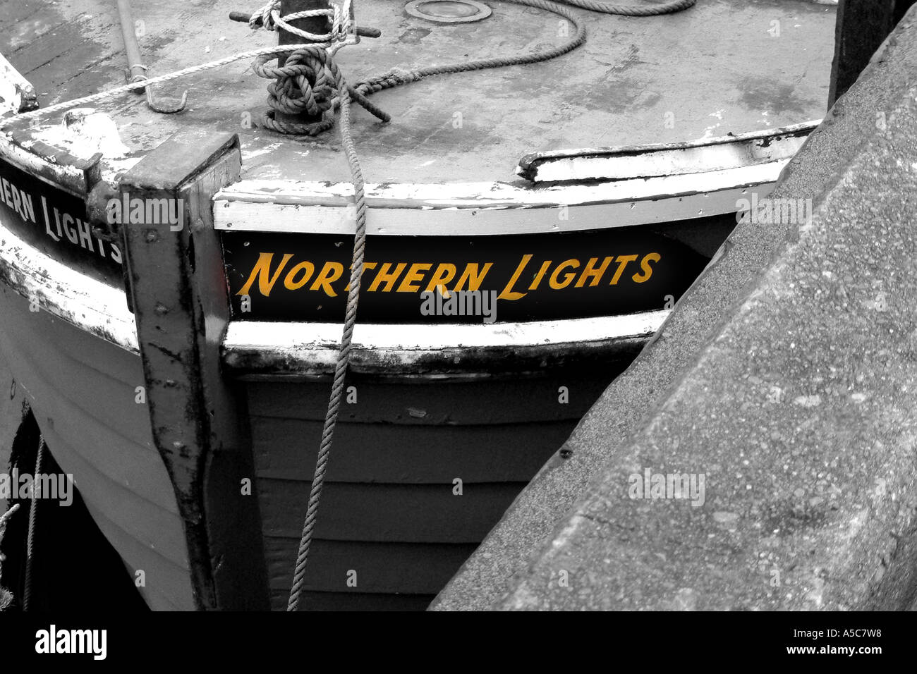Stylised black and white image of fishing boat with Northern Lights name in original yellow colour - Stock Image