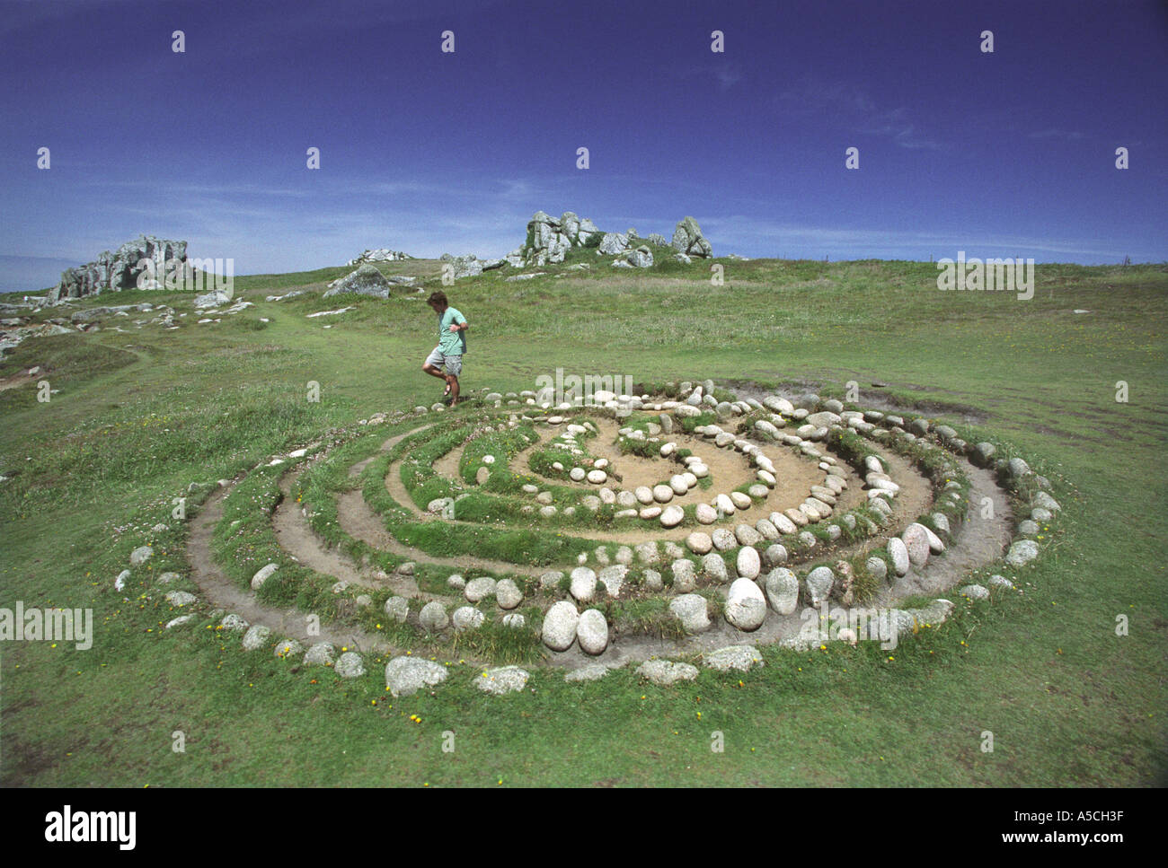 A walker steps through Troy Town Maze on the island of St Agnes Isles of Scilly built around 200 years ago - Stock Image