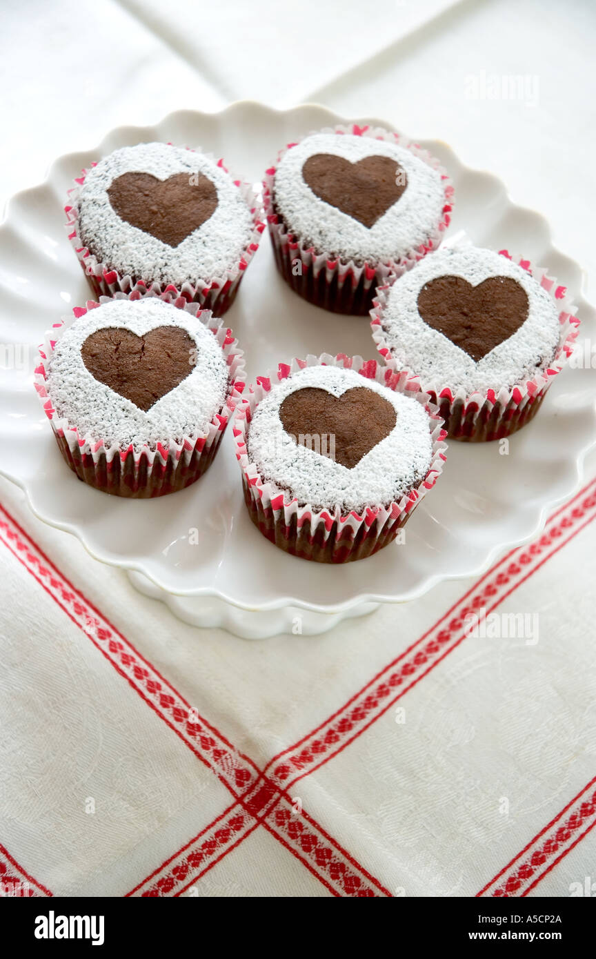 Chocolate muffins with heart shaped decoration of icing sugar