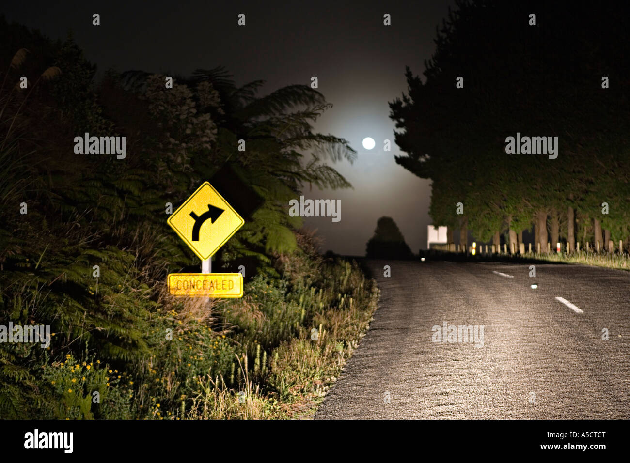 Moonset over road at night - Stock Image