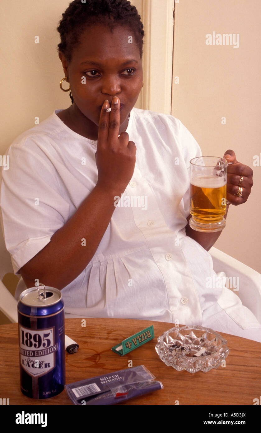 3b871bb5ce black heavily pregnant woman drinking glass of beer or lager and smoking at same  time