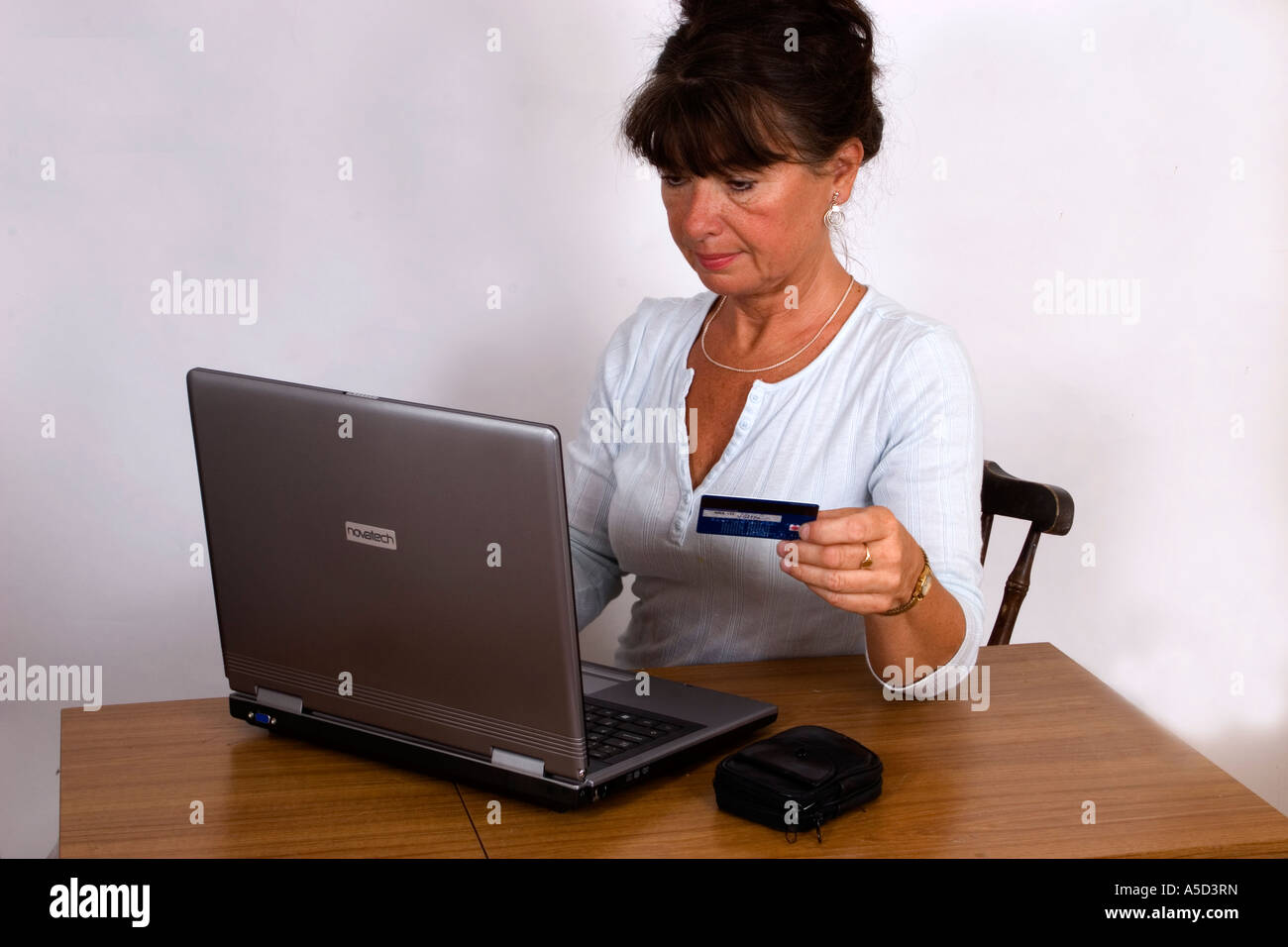 Middle aged woman on laptop computer holding credit or debit card in hand - Stock Image