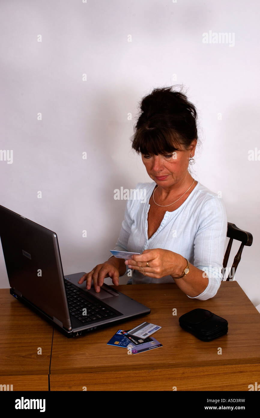 Middle aged woman on laptop computer using credit or debit card - Stock Image