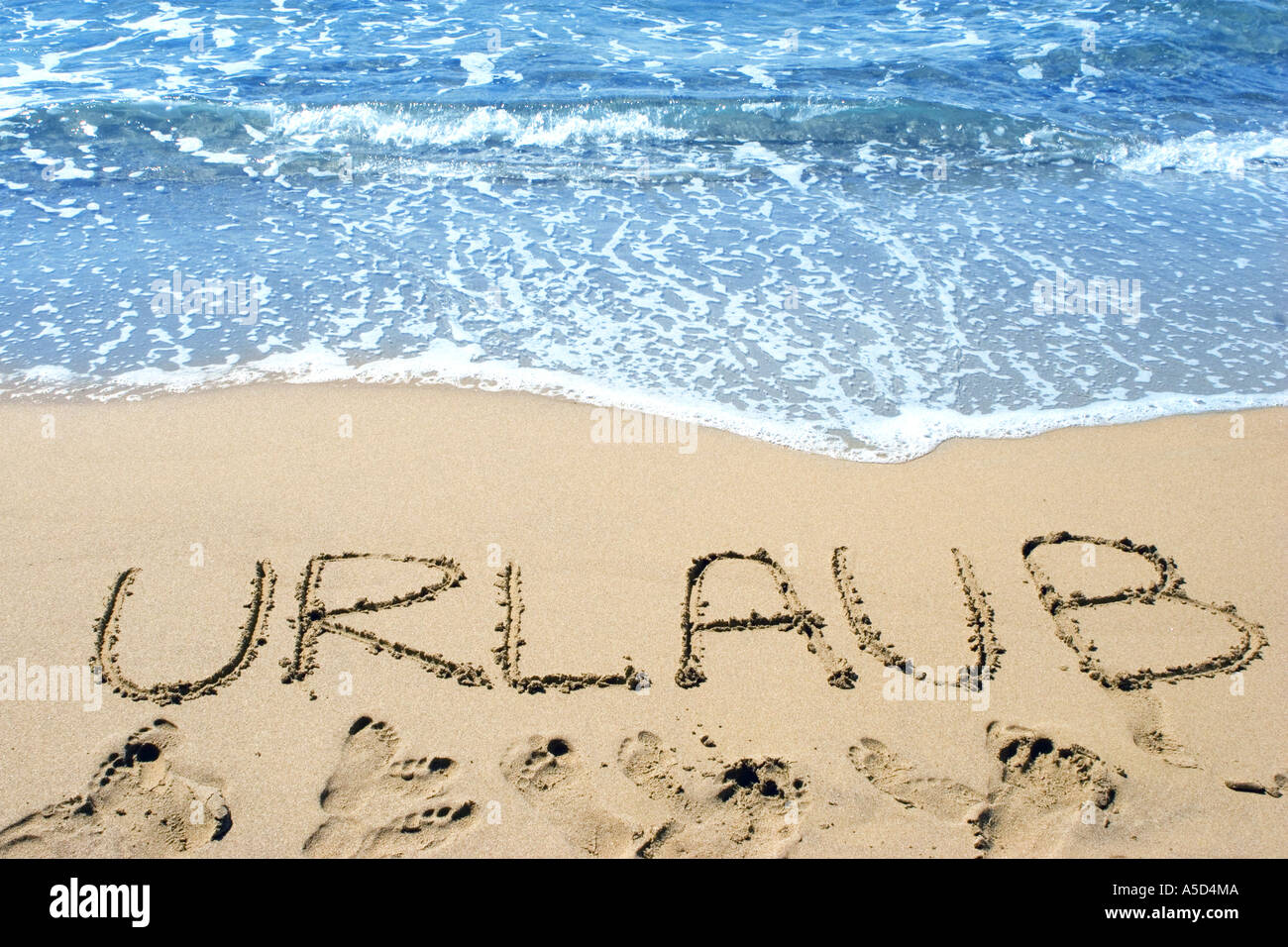 Word (Vacation) written in sand on beach - Stock Image