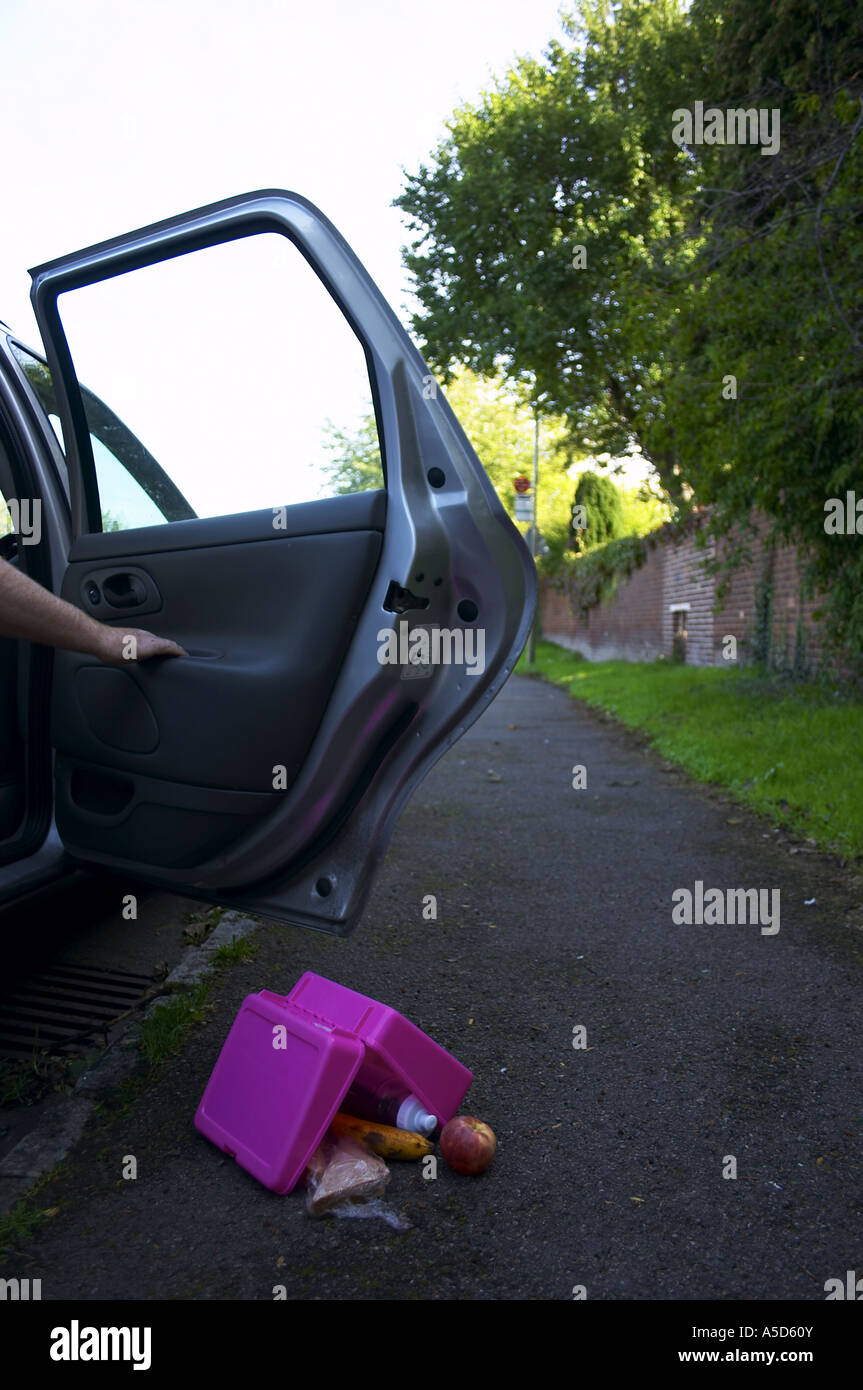 Car pulled up at kerb with dropped or discarded lunch box suggesting child has been abducted - Stock Image