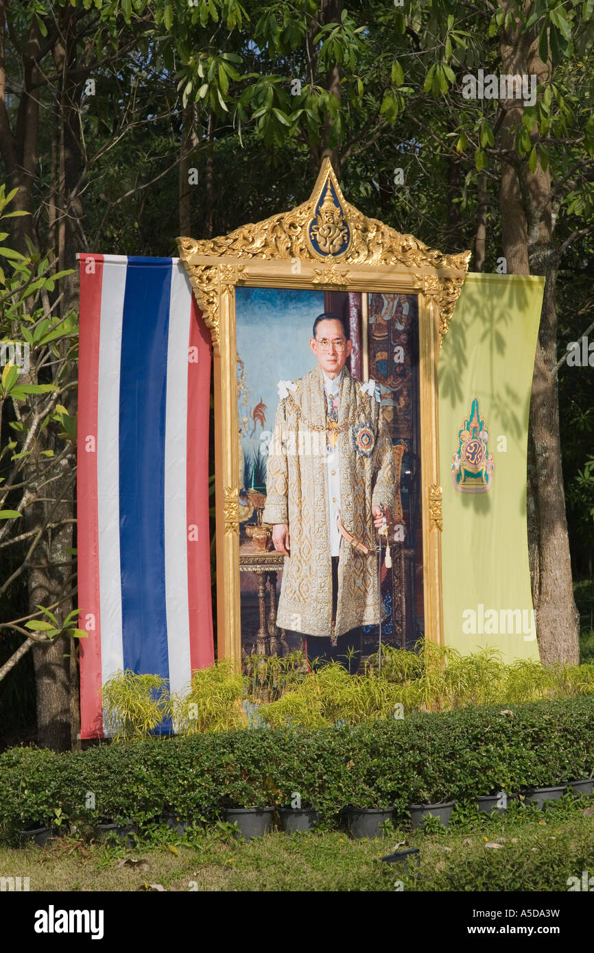 Roadside poster of the revered King Bhumibol Adulyadej  draped with national flag and royal colours - Stock Image