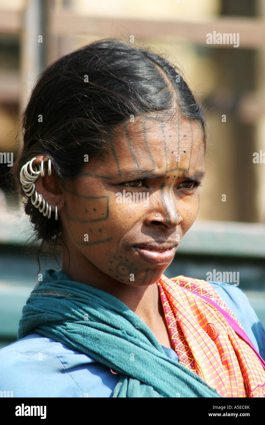 Indian Kutia Kondh tribal woman at a weekly market with  the traditional tattoo marking on her face and earrings, - Stock Image