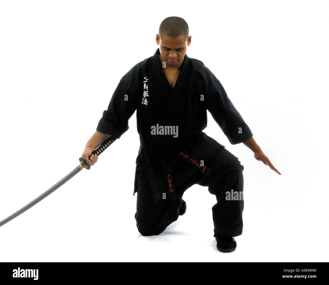 black belt karate instructor with sword in finished position with