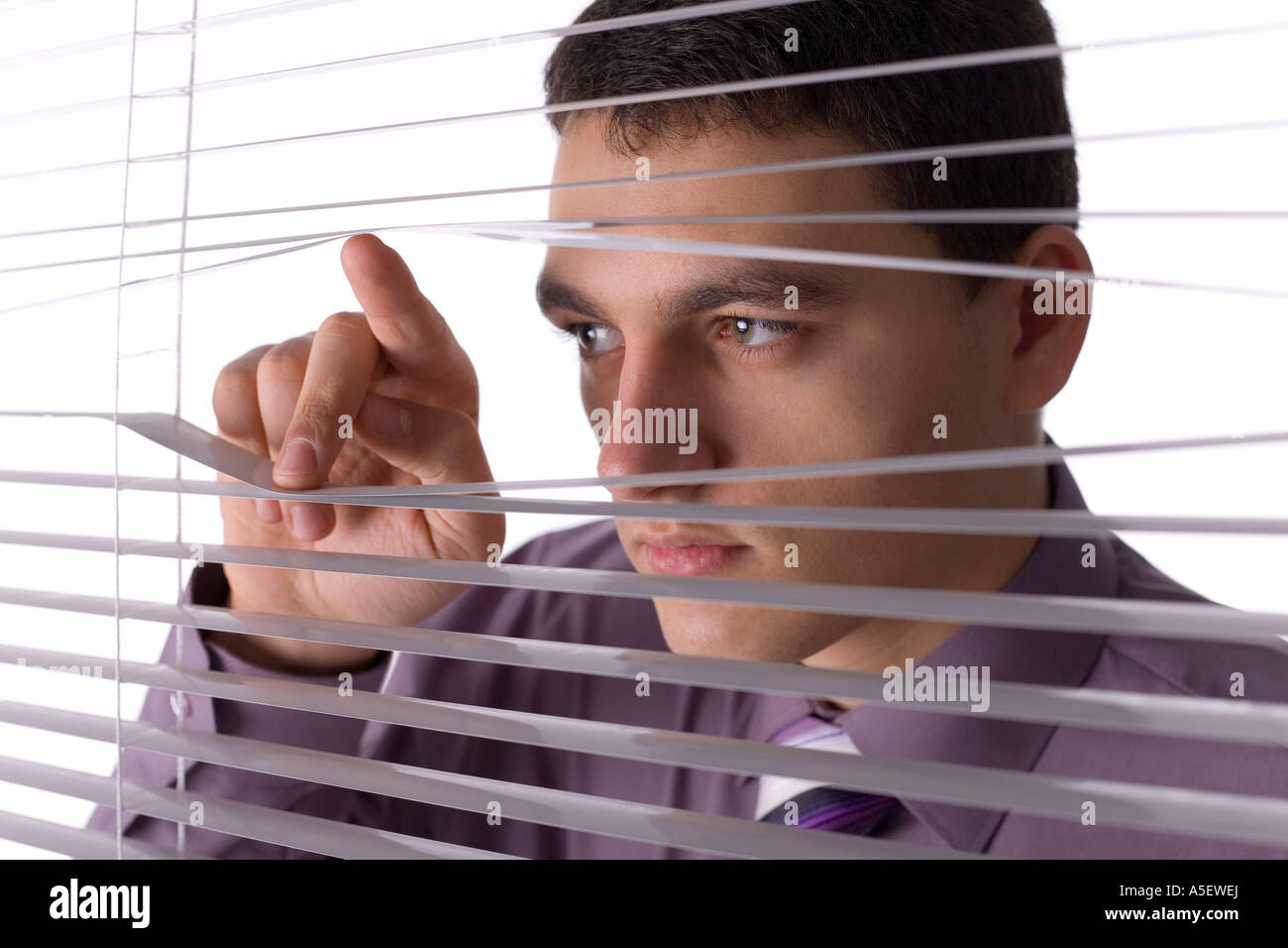 Young man looking through the blind White background in studio - Stock Image