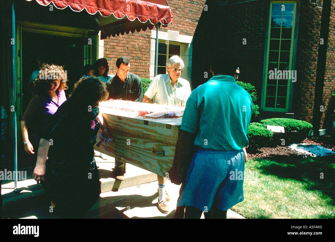 Family carrying grandma in home made wooden coffin age 30 and 60. WesternSprings Illinois USA - Stock Image