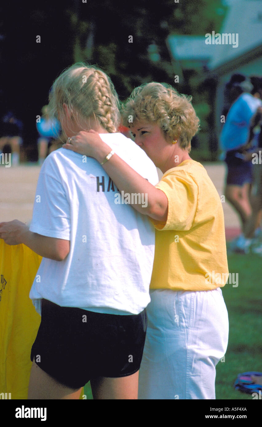 Mom comforting daughter at track meet age 15 and 35. St Paul Minnesota USA - Stock Image