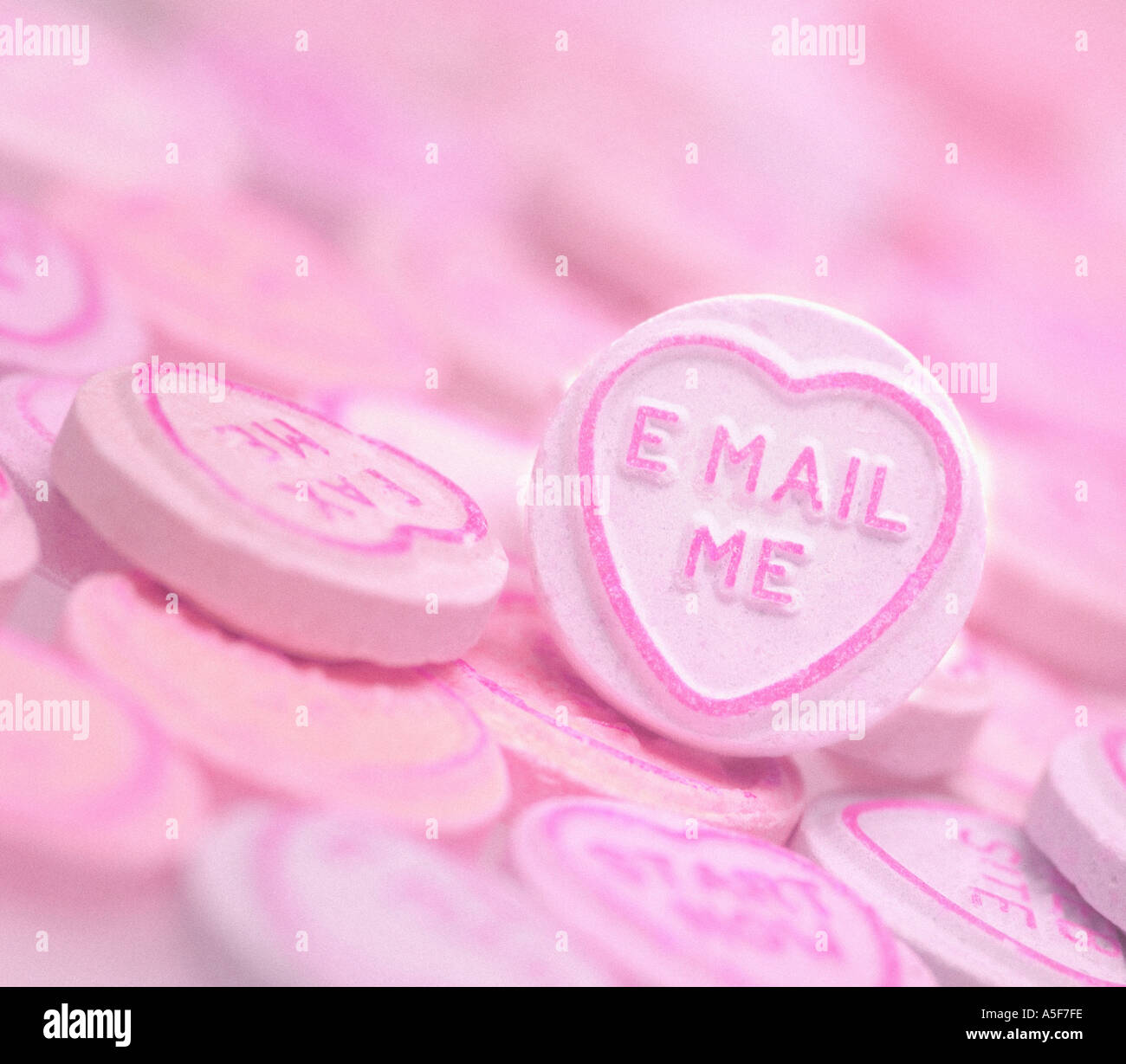 Pink sweets with E MAIL ME text - Stock Image