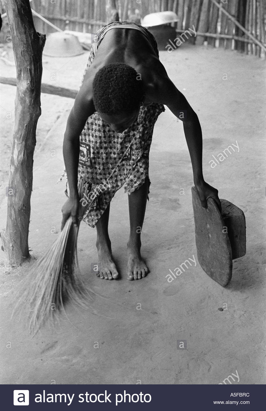 Girl sweeping the floor in a village Guinea Bissau 1994 - Stock Image