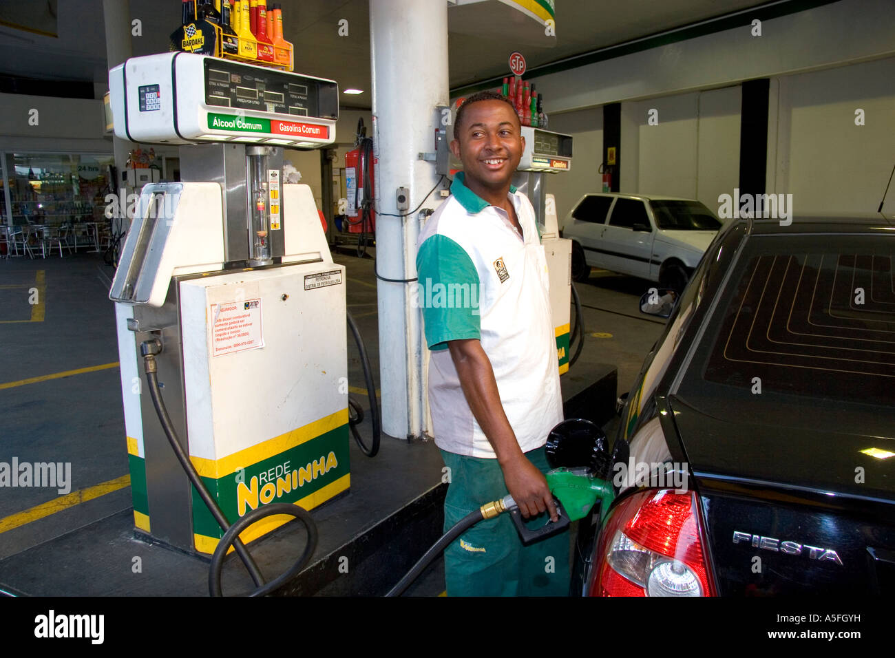 attendant at a gas station pumping alcohol into a car in sao paulo brazil