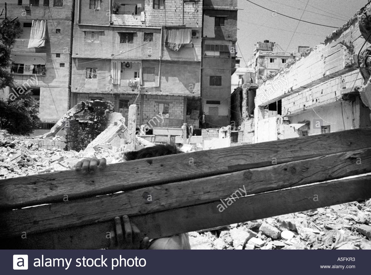 Carrying wooden beams on the site of a demolished building Beirut - Stock Image