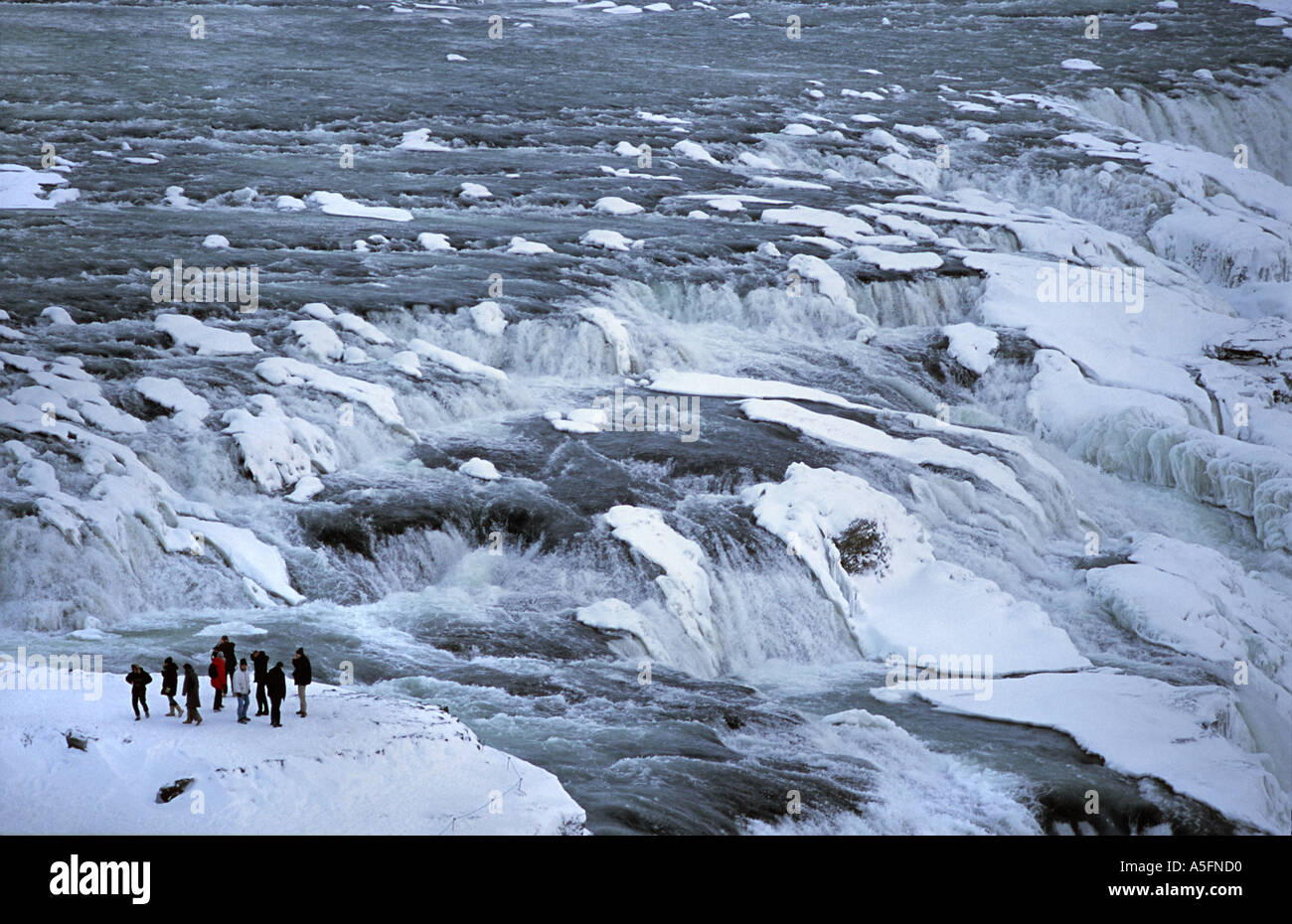 A group of tourists stand beside the powerful gushing waters of Gullfoss Golden Falls in the midst of winter Southern Iceland - Stock Image